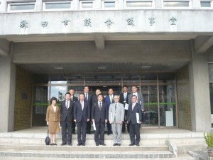 秋田市議会の議会棟前で議会運営委員会の集合写真。